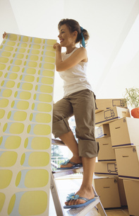 Low angle view of a young woman hanging wallpaperの写真素材 [FYI02126854]