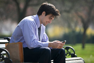 A businessman sitting on a bench, using his mobile phoneの写真素材 [FYI02126861]