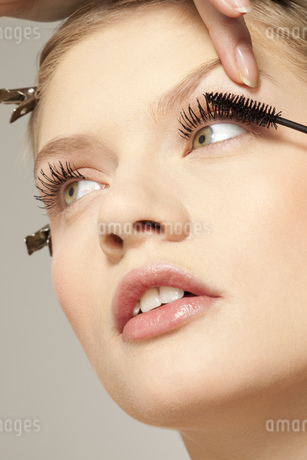 Young woman applying make up to eyelashesの写真素材 [FYI02126862]