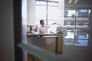 View of businessman sitting at desk in office settingの写真素材 [FYI02126895]