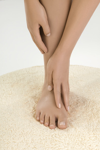 Close up of woman's hands caressing bare foot on rugの写真素材 [FYI02126948]