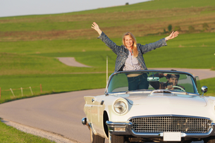 Couple Driving On Country Road In Open Top Classic Carの写真素材 [FYI02126962]