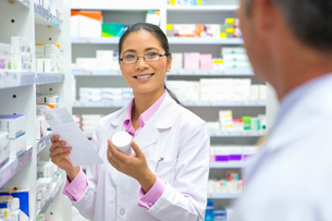Pharmacist holding medication pack and prescription, talking to colleague in pharmacyの写真素材 [FYI02126963]