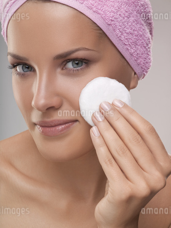 Portrait of young woman with towel on head holding make-up powder, studio shotの写真素材 [FYI02126978]