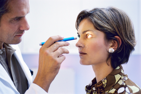 Portrait of a male doctor shining a light into a young woman's eyesの写真素材 [FYI02126980]