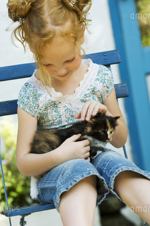 Young girl sitting in chair with kitten outdoorsの写真素材 [FYI02126996]