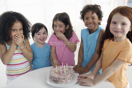 Group of children smiling around birthday cake indoorsの写真素材 [FYI02127003]