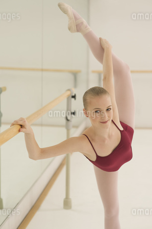A ballet dancer stretching her back leg whist holding on to the barreの写真素材 [FYI02127020]