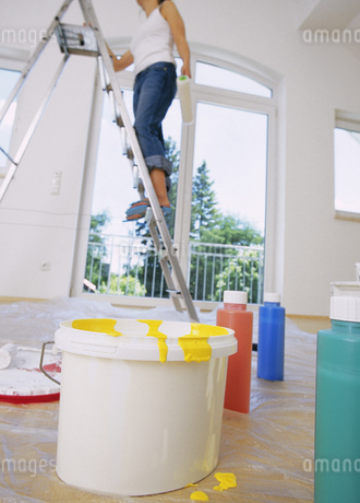View of a young woman standing on a ladder with a bucket of paint in foregroundの写真素材 [FYI02127024]