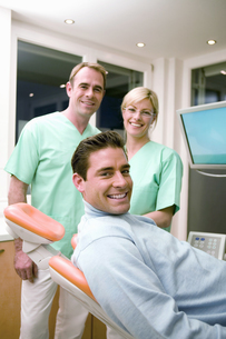 Male patient smiling with dentist and assistant in backgroundの写真素材 [FYI02127045]