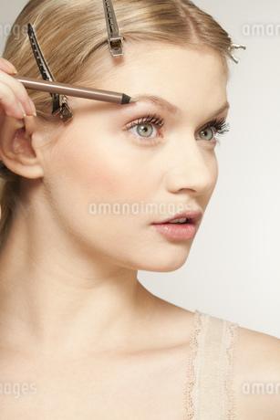 Young woman using eyebrow pencilの写真素材 [FYI02127060]