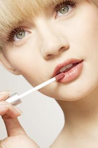 Portrait of young woman applying lip glossの写真素材 [FYI02127110]
