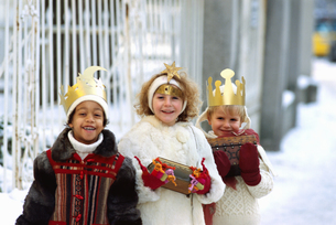 Portrait of a three young children dressed as the Three Kings walking in the snowの写真素材 [FYI02127112]
