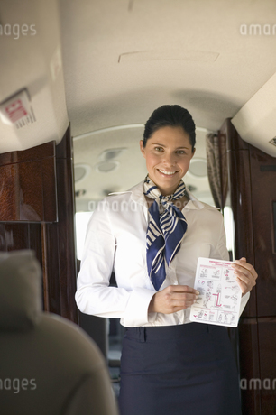 Female flight attendant giving safety presentation on airplaneの写真素材 [FYI02127130]