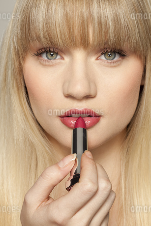 Young woman applying red lipstickの写真素材 [FYI02127144]