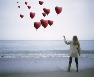 View of a woman letting heart-shaped balloons go on the beachの写真素材 [FYI02127160]