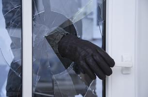 Burglar reaching through broken glass on doorの写真素材 [FYI02127161]