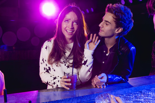 Young man bothering woman at bar in nightclubの写真素材 [FYI02127163]
