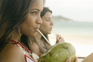 Woman drinking through straw from coconutの写真素材 [FYI02127169]