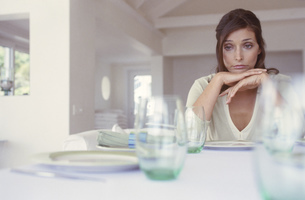 Portrait of a young woman sitting at an empty tableの写真素材 [FYI02127176]