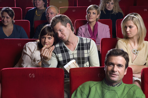 Jealous woman watching couple in movie theaterの写真素材 [FYI02127202]