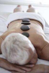 Senior man getting spa stone treatmentの写真素材 [FYI02127203]