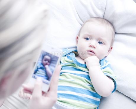 Teenage girl taking photograph of baby boyの写真素材 [FYI02127221]