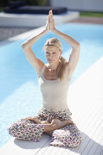 Mature woman in yoga pose at poolside of outdoor poolの写真素材 [FYI02127228]