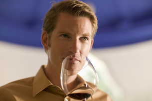 Man smelling red wine in glass at wine tastingの写真素材 [FYI02127266]