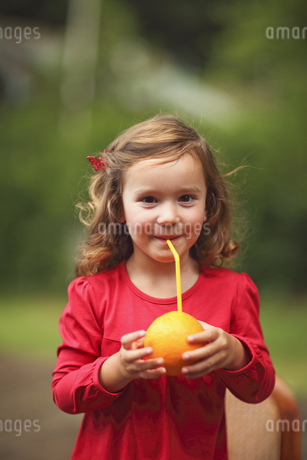 A young girl drinking orange juice through a strawの写真素材 [FYI02127272]