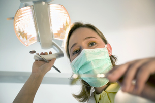 Female dentist wearing surgical mask and holding dental toolsの写真素材 [FYI02127328]