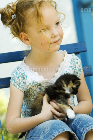 Young girl sitting in chair with kitten outdoorsの写真素材 [FYI02127329]
