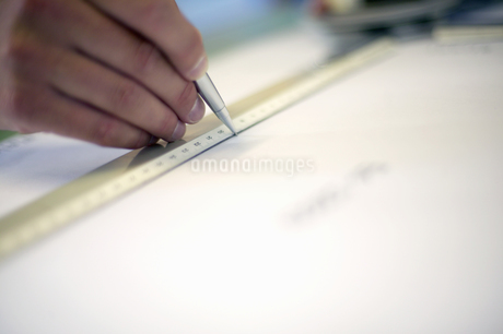 Close up of a hand using a ruler to draw a lineの写真素材 [FYI02127330]