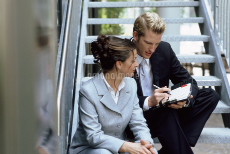 View of a businessman and a businesswoman sitting on a staircase conversingの写真素材 [FYI02127354]