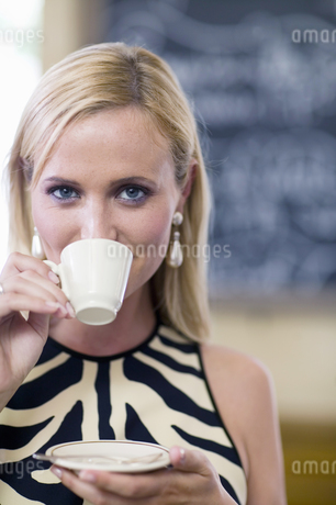 Close up of woman drinking espresso in restaurantの写真素材 [FYI02127358]