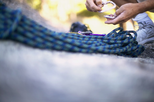 Detail view of rock climbing rope with man in backgroundの写真素材 [FYI02127365]
