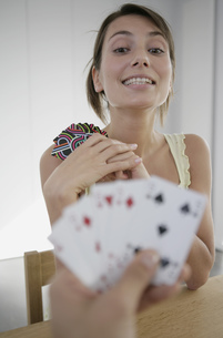 Portrait of a young woman playing cards with her opponent's hand in foregroundの写真素材 [FYI02127401]