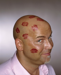 Bald man with lipstick kisses all over his headの写真素材 [FYI02127419]