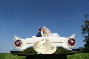 Bride And Groom In Open Top Classic Car On Wedding Dayの写真素材 [FYI02127436]