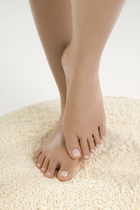 Close up of woman's bare feet on rugの写真素材 [FYI02127451]
