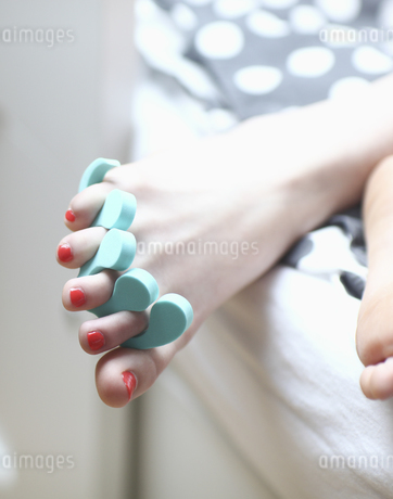 Close up of foot with nail polish and toe dividerの写真素材 [FYI02127470]