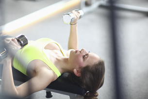 Teenage girl bench pressing with dumb bells in gymの写真素材 [FYI02127471]