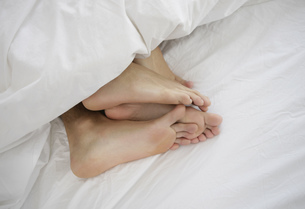 View of a couples feet in bedの写真素材 [FYI02127493]