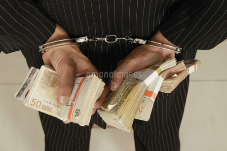 Thief holding Euros in handcuffs, rear viewの写真素材 [FYI02127497]