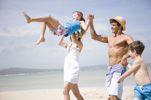 Man and woman swinging daughter on beachの写真素材 [FYI02127501]