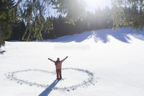 Young woman making heart shape in snowの写真素材 [FYI02127506]