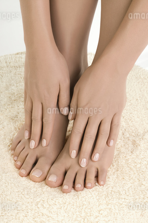 Close up of woman's hands caressing bare feet on rugの写真素材 [FYI02127552]