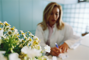 View of a young female doctor with a bouquet of flowers in foregroundの写真素材 [FYI02127573]