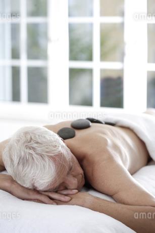 Senior man getting spa stone treatmentの写真素材 [FYI02127584]