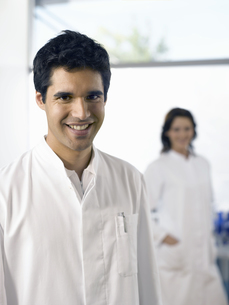 Male scientist smiling with co-worker in backgroundの写真素材 [FYI02127600]